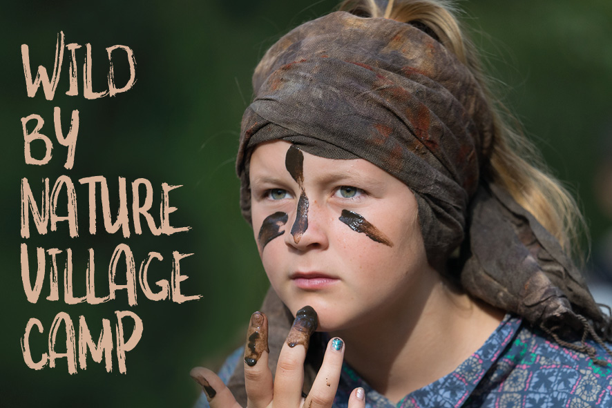 "Young woman putting mud on her face, words ""Wild By Nature Village Camp"""
